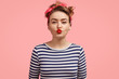 Leinwanddruck Bild - Beautiful young female gives kiss at camera, shows brightly red lips, has make up, wears retro style clothing, poses against pink background. Charming pinup girl in striped sweater flirts with someone