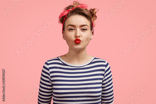 Fotobehang Kapsalon Beautiful young female gives kiss at camera, shows brightly red lips, has make up, wears retro style clothing, poses against pink background. Charming pinup girl in striped sweater flirts with someone