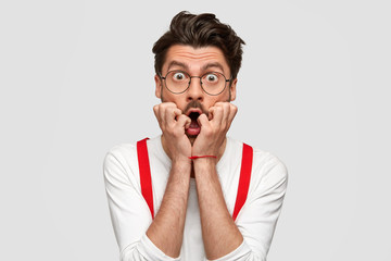 Portrait of puzzled scared male professor finds out about student`s failure, looks nervously, has trendy hairstyle, wears formal white shirt and red suspenders. Omg, what I have done! Frightened man