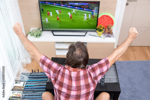 Aluminium Voetbal Back view of excitement man with gesturing hands up how watching soccer in television at home. Rear view of man watching sport in TV. Football fan celebrates goal.