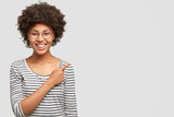Horizontal portrait of happy dark skinned female with Afro hairsyle giggles joyfully, has broad smile with white teeth, indicates aside at blank space for your advertising content. Emotions concept - 208516881