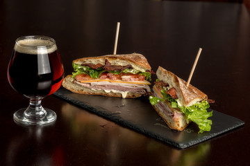 Club sandwich cut in half with a frosty glass of beer