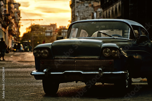 Old classic car in a street of havana, cuba with sunset on background