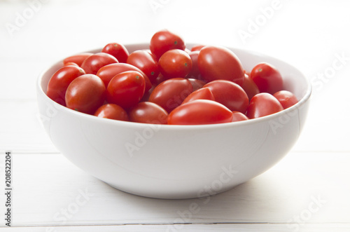 Sticker Grape Tomatoes in a White Bowl on a White Wood Table