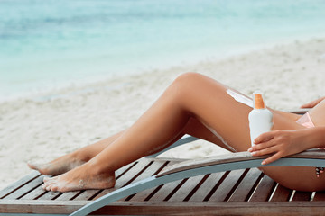 Young woman applying sunscreen lotion, holding sun cream bottle on the beach. Sun protection. Skin care