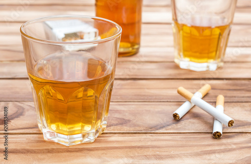 Glasses of whisky with cigarettes and bottle of whiskey on wooden background. Close up.