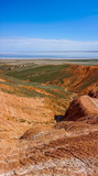 Landscape with red mountains on the background of flat steppe and blue lake Baskunchak - 208535813