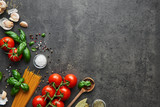 Food background for tasty Italian dishes with tomato. Various cooking ingredients with spaghetti and spoon. Top view with copy space. - 208537073