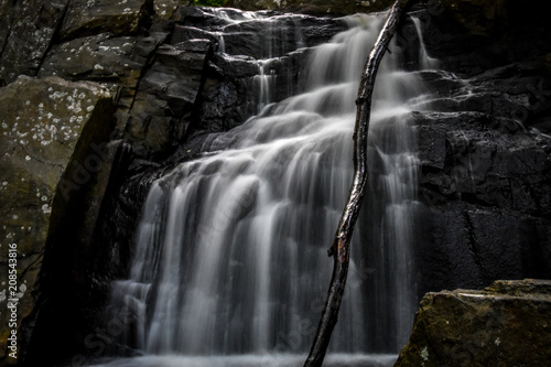 Waterfall Cascading Over Stone - 208543816
