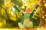Happy woman throwing autumn leaves in park - 208546280