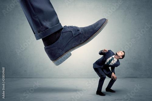Leinwanddruck Bild Demoralised employee symbolized by small man getting trampled