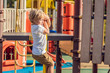 Leinwanddruck Bild - Funny cute happy baby playing on the playground. The emotion of happiness, fun, joy
