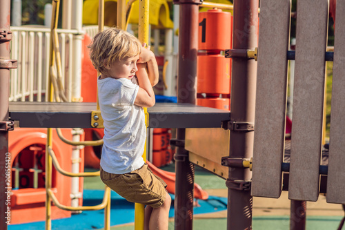 Leinwanddruck Bild Funny cute happy baby playing on the playground. The emotion of happiness, fun, joy