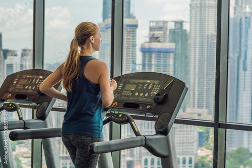 sport, fitness, styl życia, technologia i ludzie pojęcie - kobieta ćwiczy na karuzeli w gym przeciw tłu duży miasto