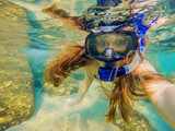 Woman snorkeling in tropical waters in front of exotic island - 208554092