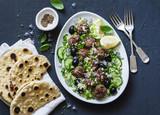 Greek meatballs with avocado greek yogurt sauce, couscous and whole grain flatbread on a dark background, top view. Mediterranean style food - 208560009