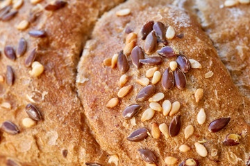 Close up picture of a whole wheat bread crust with flax and sesame seeds, selective focus.