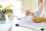 Close up audit woman calculate on paper document financial data. - 208566690