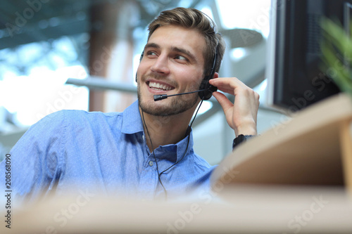 Leinwanddruck Bild Smiling friendly handsome young male call centre operator.
