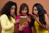 Three African Woman Using Digital Tablet While Looking Surprised And Shocked - 208568472