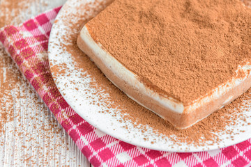 Homemade layered cottage cheese souffle dessert with cocoa on white wooden table