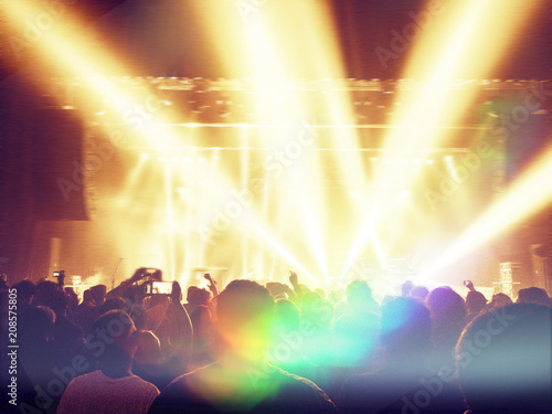 Foto Murales Concert crowd with lens flare and haze, stage is visible ahead.