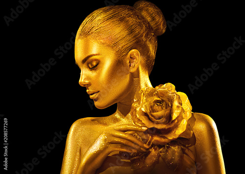 Leinwanddruck Bild Golden skin woman with rose. Fashion art portrait. Model girl with holiday golden glamour shiny professional makeup. Gold jewellery, accessories
