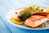 Grilled salmon with vegetables on blue wooden table - 208580494