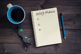 Notebook with 2019 plans massage, pencil, glasses and cup of coffee on wood background. - 208583008