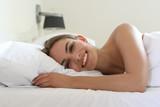 Hübsche junge Frau liegt lachend und in Seitenlage in einem Bett - 208583255