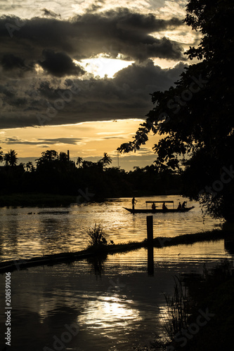 Foto Murales A small wooden boat crossing a river in rural thailand, at sunset.