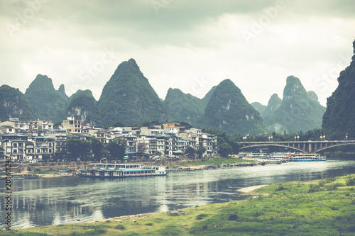 Fotobehang Guilin Scenic summer sunny landscape at Yangshuo County of Guilin, China. View of beautiful karst mountains and the Li River (Lijiang River) with azure water. Amazing green hills on blue sky background.