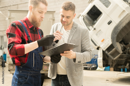 fototapeta na ścianę Young bearded auto technician showing inspection checklist to male customer after finished maintenance in repair workshop
