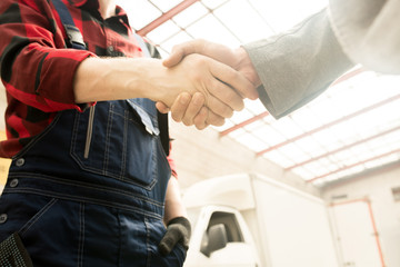 Low angle view of unrecognizable male auto technician in workwear shaking hands with car owner in service garage