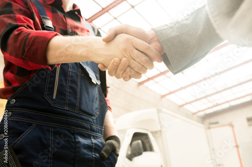 Fridge magnet Low angle view of unrecognizable male auto technician in workwear shaking hands with car owner in service garage