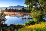 Berge im Morgenlicht spiegeln sich in einem Teich - 208608293