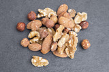 bunch of hazelnuts, almonds, and nuts on black background - 208610852
