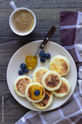 Sticker Cottage cheese pancakes (syrniki) with sour cream, orange jam and fresh blueberries on a plate. Breakfast or lunch concept.