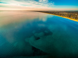 Smooth shallow ocean water surface with cloud reflections near coastline at sunset - 208626246