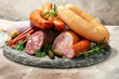 Leinwanddruck Bild - Food tray with delicious salami, ham,  fresh sausages, cucumber and herbs. Meat platter