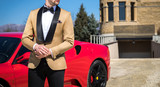 Man in custom tailored tuxedo, suit posing outdoors in front of expensive car