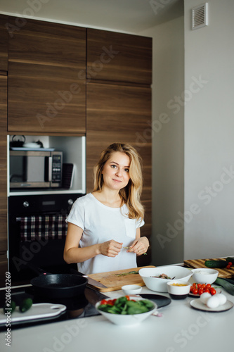 Young positive girl, recently got married , learning to cook home made meal from fresh and healthful diet products. Blonde woman looking at camera at kitchen background. - 208632269