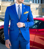 Man in expensive custom tailored suit posing in front of expensive car outdoors