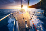 Sunset at the Sailboat deck while cruising / sailing at opened sea. Yacht with full sails up at the end of windy day. Sailing theme - background. Yachting design. - 208632816