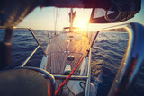Sunset at the Sailboat deck while cruising / sailing at opened sea. Yacht with full sails up at the end of windy day. Sailing theme - background. Yachting design. - 208632884