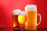 Mug and glass of beer close-up with froth over red background - 208645045