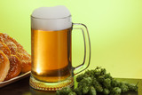 Pint of beer with ingredients for homemade beer on yellow with pretzel - 208645058