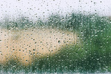 Water drops on window in a rainy day, blurry view on background