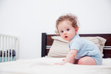 Curly little baby boy sitting on a bed in a bedroom. - 208657250
