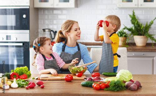 mother with children preparing vegetable salad .